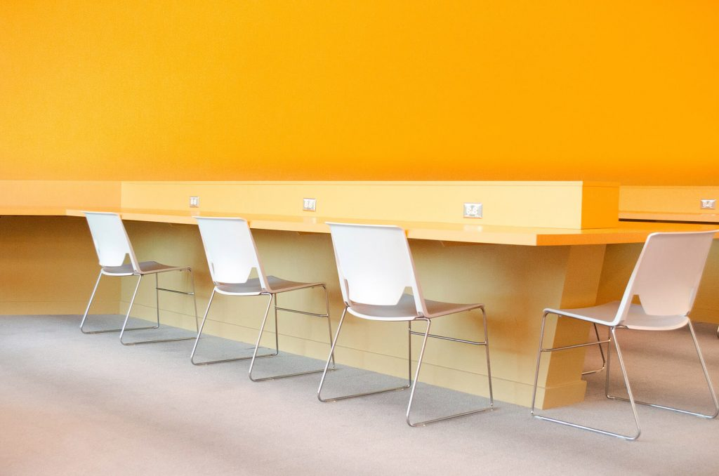 An empty office with white chairs in front of a yellow wall.
