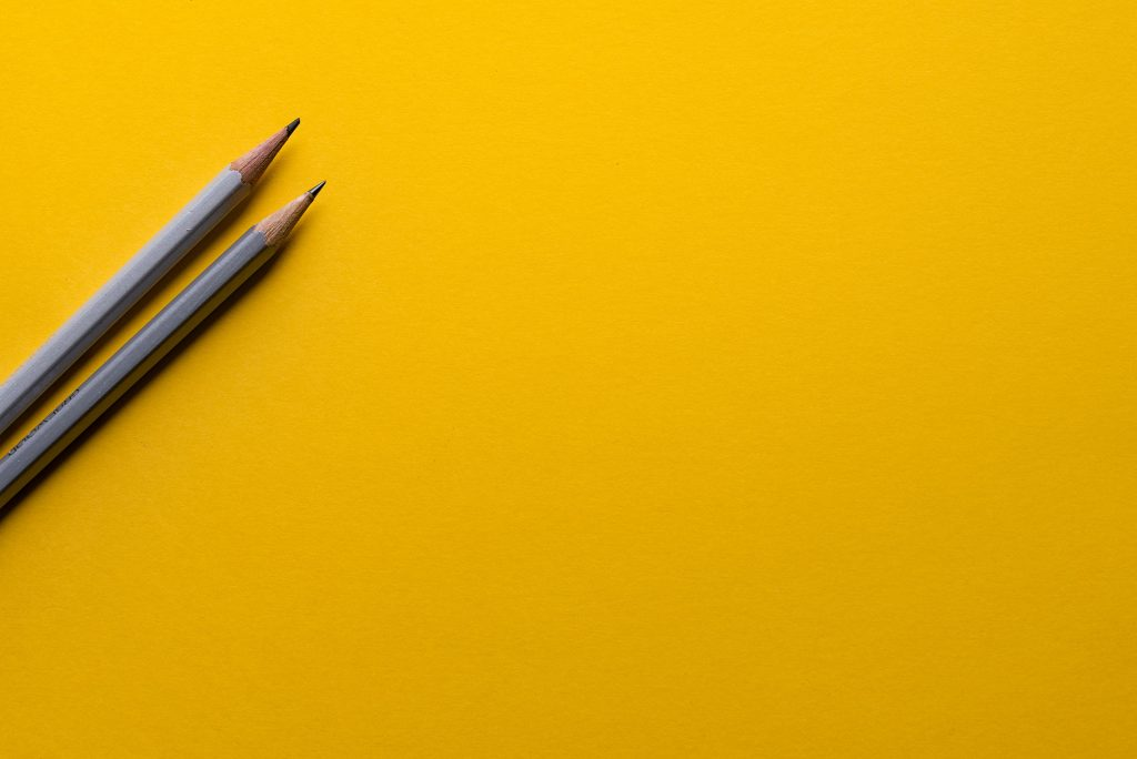Two pencils lay on a bright yellow background
