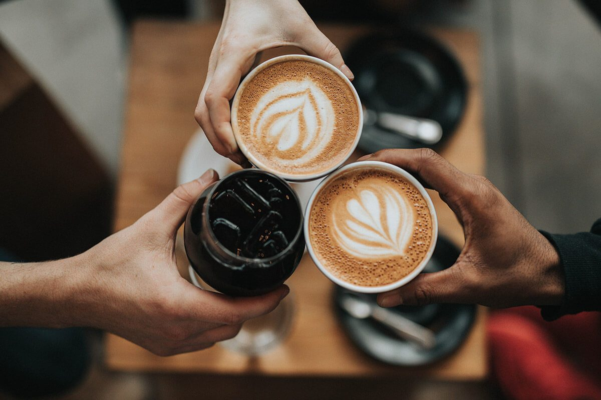 Friends raising mugs of coffee in a toast to a successful job search
